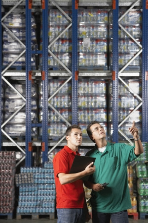 inventory: Two Men standing side by side gesturing in warehouse with full shelves