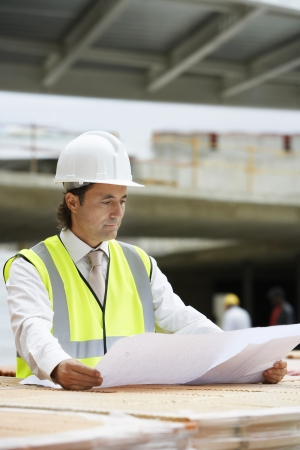 spaniards: Construction worker examining building plans on site LANG_EVOIMAGES