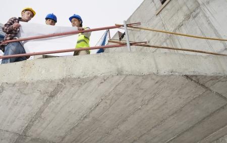 spaniards: Construction team examining building plans on site