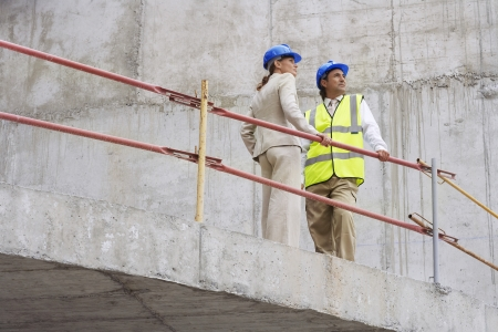 leaning by barrier: Architect and construction manager on site