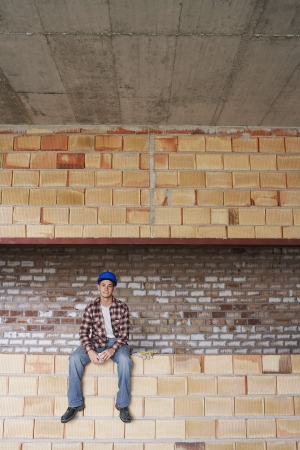 spaniards: Construction worker sitting on brick wall LANG_EVOIMAGES