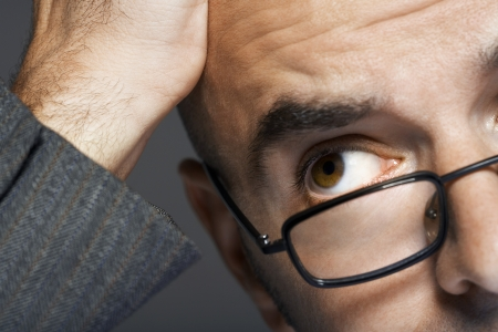 head close up: Balding businessman wearing glasses hand on head close up LANG_EVOIMAGES