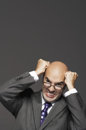 pounding head: Bald businessman fists on head pounding head making a face
