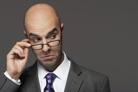 superiority: Balding businessman hand on glasses making a face