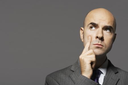 bald man: Hombre de negocios calvo con la mano en la barbilla pensando