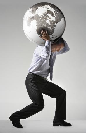 anguished: Businessman struggling carrying globe on shoulders side view LANG_EVOIMAGES