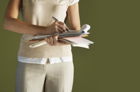 dictating: Young woman standing holding notepad writing mid section