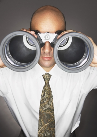 unrecognisable people: Balding Middle-aged businessman looking through large binoculars