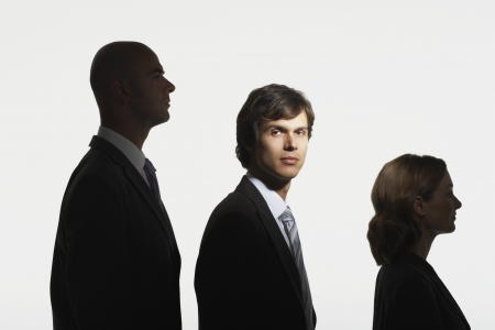 facing the camera: Businesspeople standing in row in height order middle man facing camera in spotlight