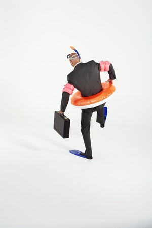 waddling: Middle-aged businessman in flippers inflatable rubber ring snorkel and goggles waddling carrying briefcase back view