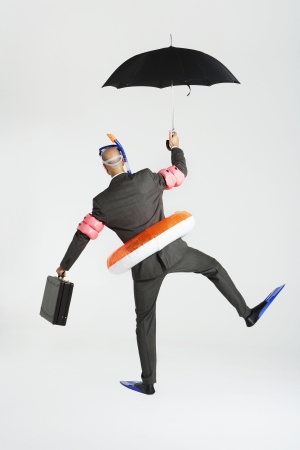 waddling: Middle-aged businessman in flippers inflatable rubber ring snorkel and goggles waddling carrying briefcase and umbrella back view LANG_EVOIMAGES