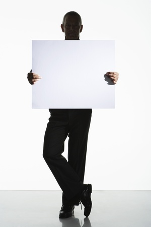 Silhouetted man standing holding large blank card Stock Photo - 18897773