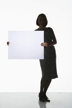 Silhouetted woman standing holding large blank card to side Stock Photo - 18897774