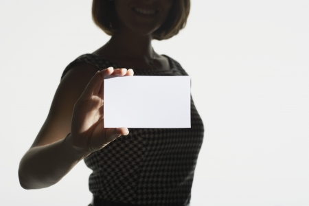 Smiling silhouetted woman standing holding large blank card mid section Stock Photo - 18897775
