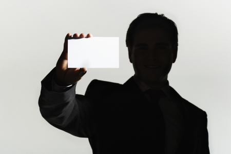 Silhouetted man standing holding large blank card Stock Photo - 18897776