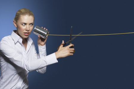terminating: Woman cutting line on tin can string phone against dark background LANG_EVOIMAGES