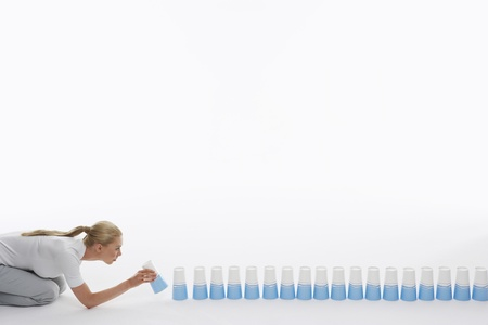 lining up: Woman lining up plastic cups on ground against white background