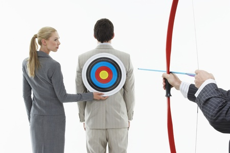 office politics: Business woman holding target to mans back while other man (close-up of hands) aims bow and arrow against white background LANG_EVOIMAGES