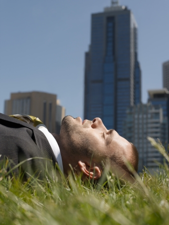 office buildings: Business man lying on grass office buildings in background