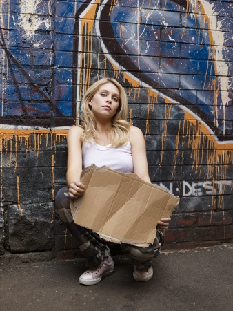 objections: Young woman squatting by brick wall pretending begging