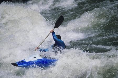 kayaker: Kayaker paddling through white water Rapids