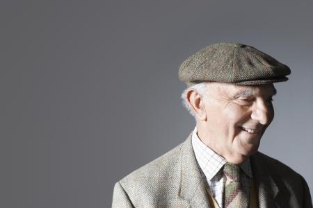 flat cap: Senior man in flat cap head and shoulders in studio