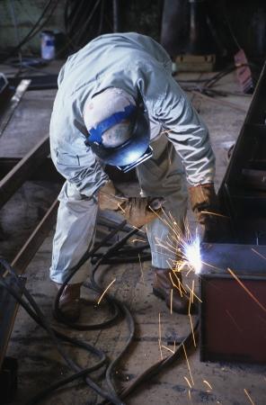 bending down: Welder bending down welding at Work