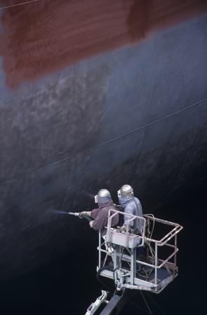 unknown age: Two People standing in crane bucket Painting Large Ship
