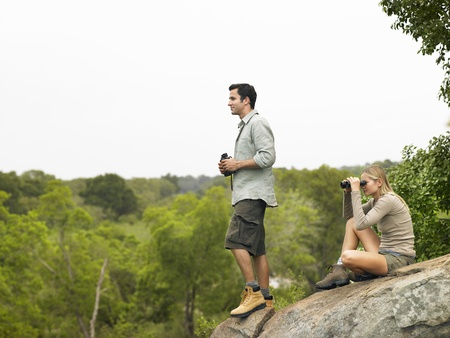ecotourism: Man and woman on rock looking at view with binoculars