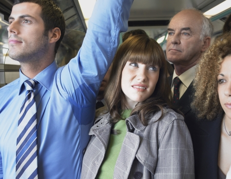 Female Commuter Standing by Mans Wet Armpit on Train Stock Photo