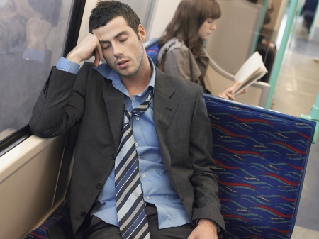 Businessman with loosened tie sleeping on Commuter Train Stock Photo - 18898364