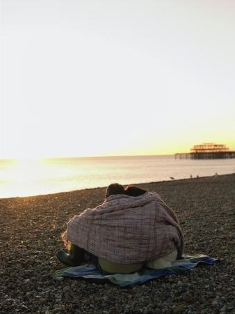 mujer mirando el horizonte: Pareja envuelta en una manta sentado en la playa viendo la puesta de sol Vista posterior