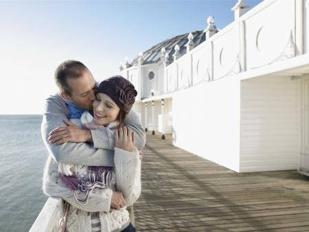 half  length: Man kissing woman standing on pier half length