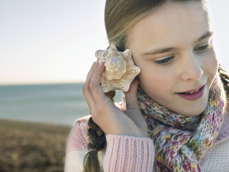 one girl only: Pre teen girl listening to seashell standing on beach close up LANG_EVOIMAGES