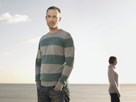 one person with others: Man standing on beach with woman in background portrait LANG_EVOIMAGES