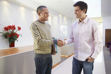 two people talking: Casually dressed Businessmen smiling Shaking Hands in Office LANG_EVOIMAGES