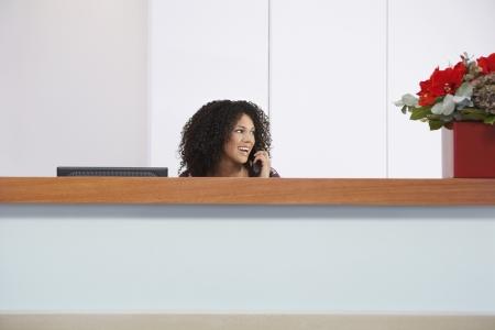recepcionista: Recepcionista sentado detrás del escritorio de recepción que habla en el teléfono