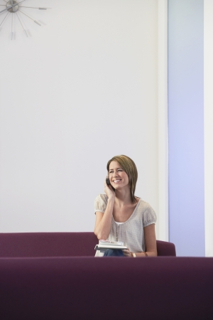 casually dressed: Smiling casually dressed Businesswoman sitting on sofa Using mobile LANG_EVOIMAGES