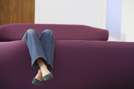 low section: Woman Relaxing upside down on Sofa low section LANG_EVOIMAGES