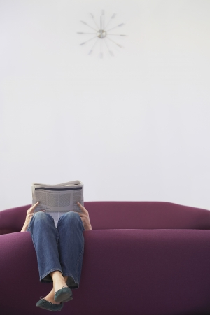 Woman Relaxing upside down on Sofa reading newspaper low section Stock Photo - 18898429