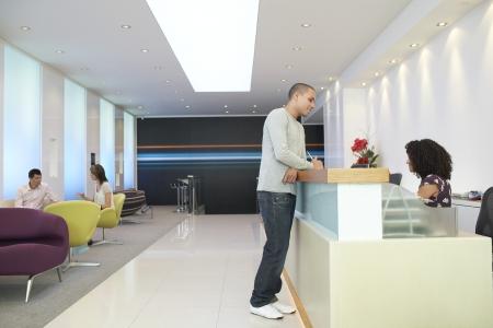 recepcionista: El hombre de pie en el mostrador de recepción Hablando con vista lateral Recepcionista