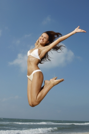 midair: Woman jumping on beach mid-air