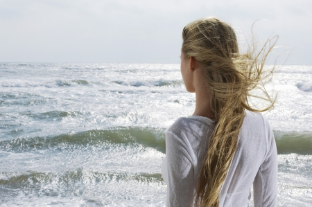 rough sea: Young woman looking at ocean back view
