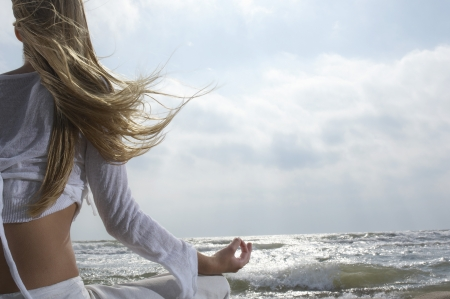 wind blown hair: Young woman meditating on beach facing ocean back view