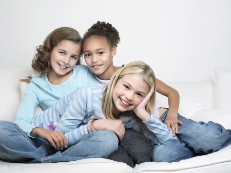 preteen girl: Young Friends sitting leaning on one another smiling