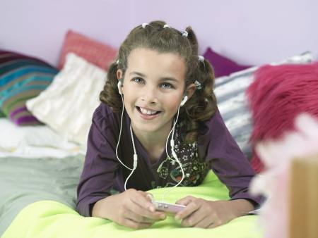 pre adolescent girls: Young Girl lying on front Listening to MP3 Player on bed LANG_EVOIMAGES