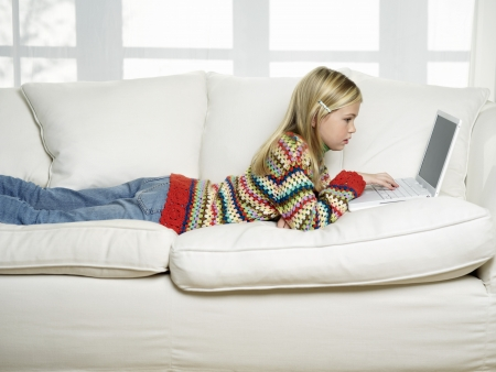 Young Girl lying on stomach on sofa using Laptop side view Stock Photo - 18898490
