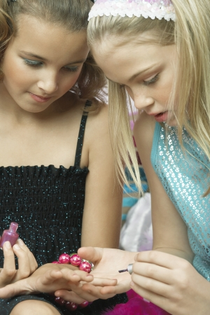 pre teen girl: Young girl applying nail polish to friends fingernails LANG_EVOIMAGES