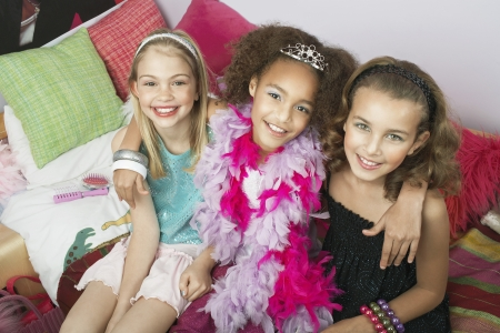 slumber: Girls sitting arms around one another on trendy sofa at a Slumber Party high angle view LANG_EVOIMAGES