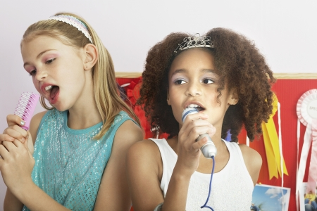 slumber: Girls using brushes microphones to sing at a Slumber Party LANG_EVOIMAGES